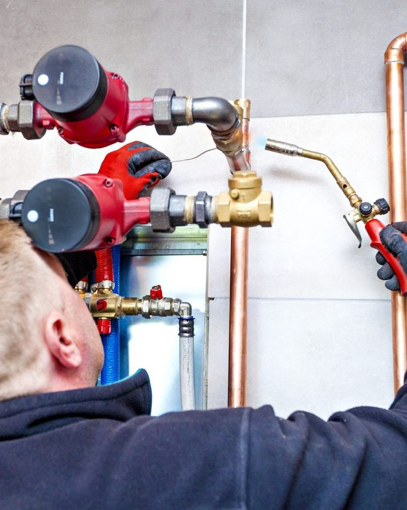 Industrial central heating system parts being fitted by plumber with blowtorch